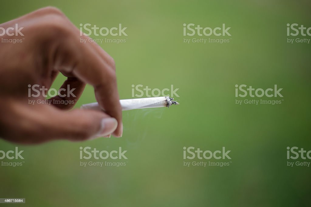 Cigarette in young female smoker hand smoking cigarette outdoors. stock photo