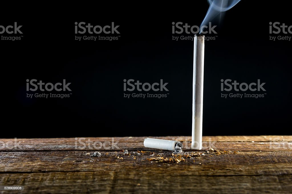 Cigarette on wood table with black background stock photo