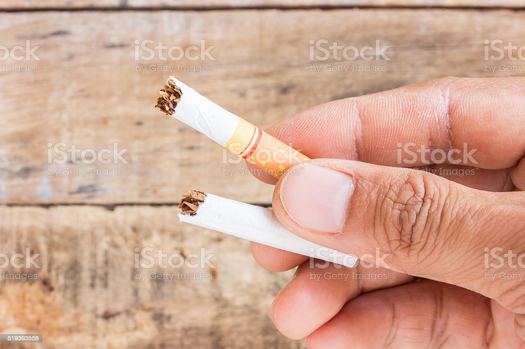 Cigarette roll in hand holding stock photo