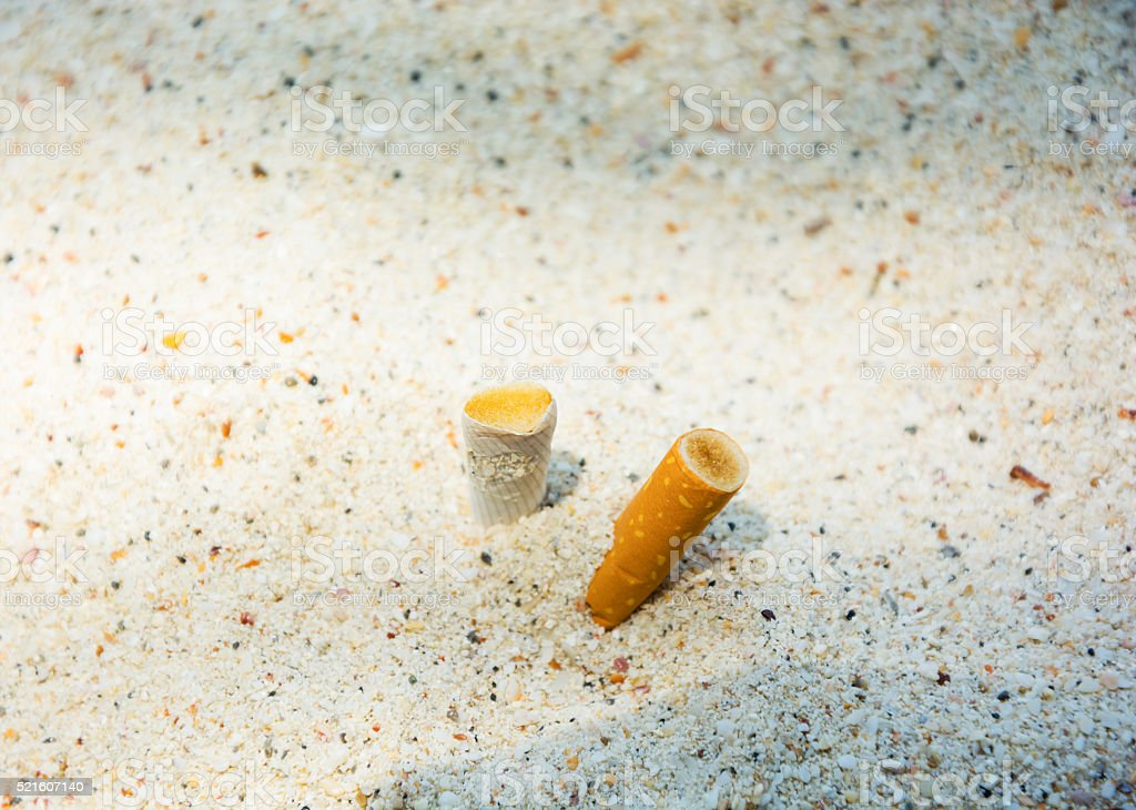 Cigarette smoked-filters on beach sand stock photo