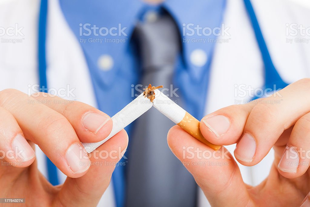 A cigarette split into half by a doctor stock photo