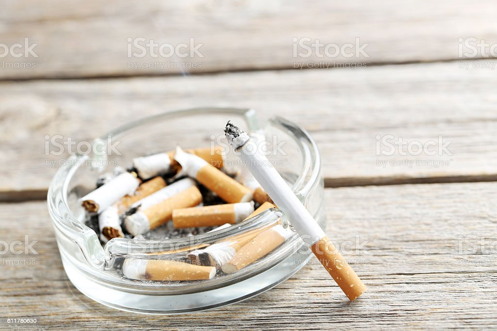 Cigarette with ash on grey wooden table stock photo