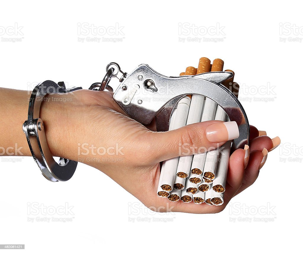 Cigarettes and handcuffs on female hand isolated. Addition concept stock photo