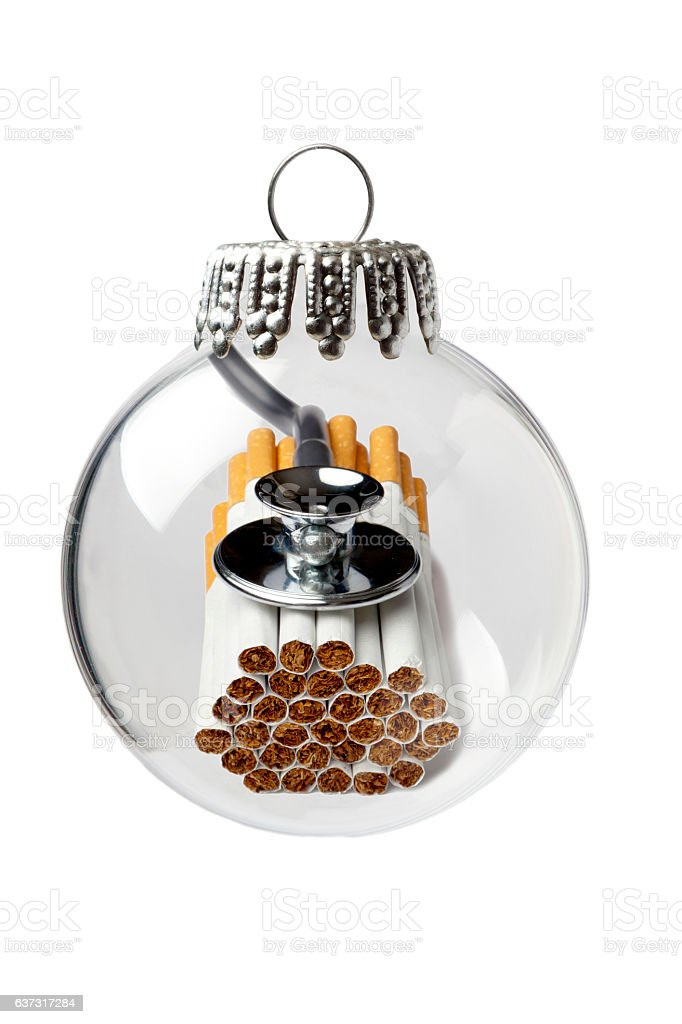 Cigarettes and Stethoscope in a Christmas Ornament stock photo