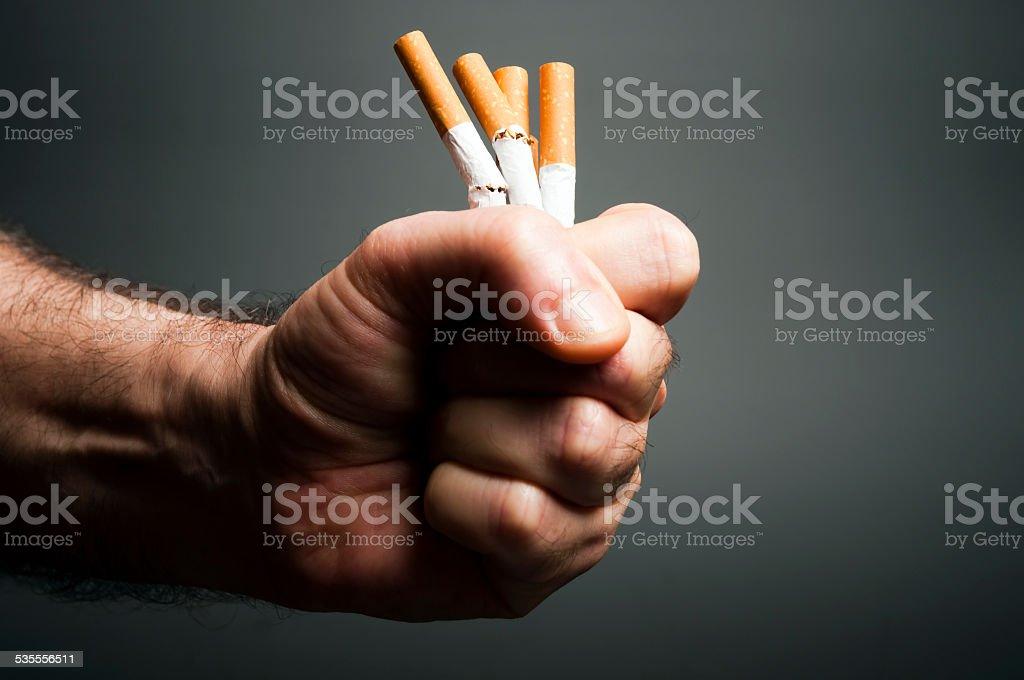 Cigarettes in fist stock photo