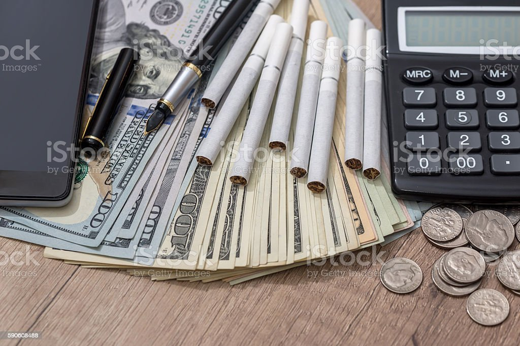 cigarettes with money on desk stock photo