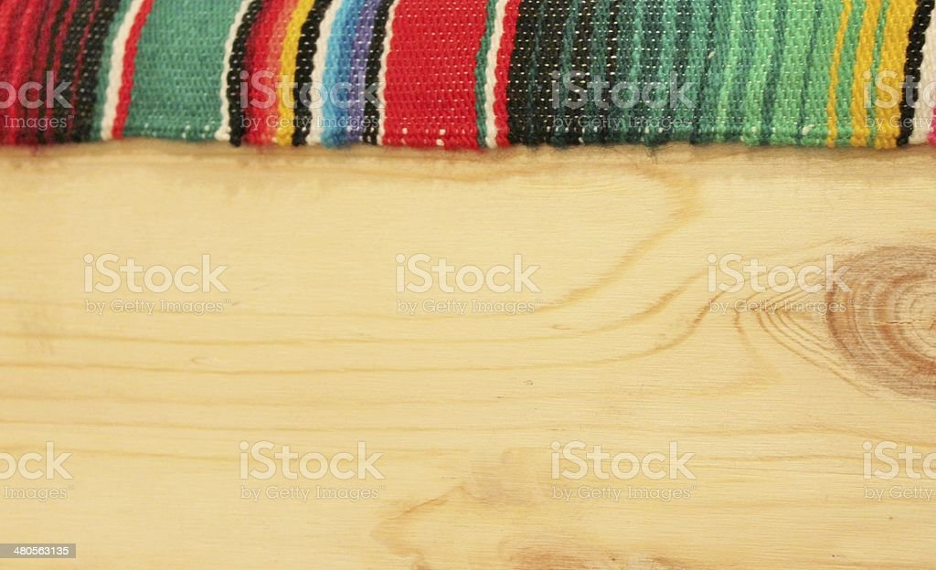 fiesta mexican poncho rug in bright colours with wooden background stock photo