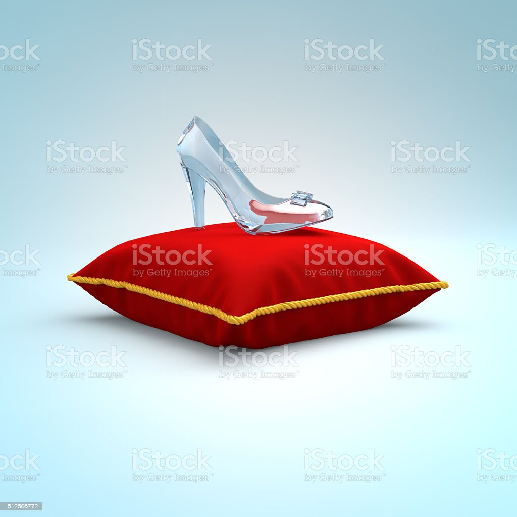 Cinderella glass slipper on the red pillow side view stock photo