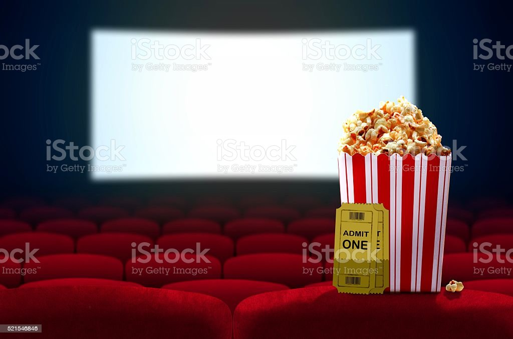 Cinema seat and pop corn facing empty movie screen stock photo