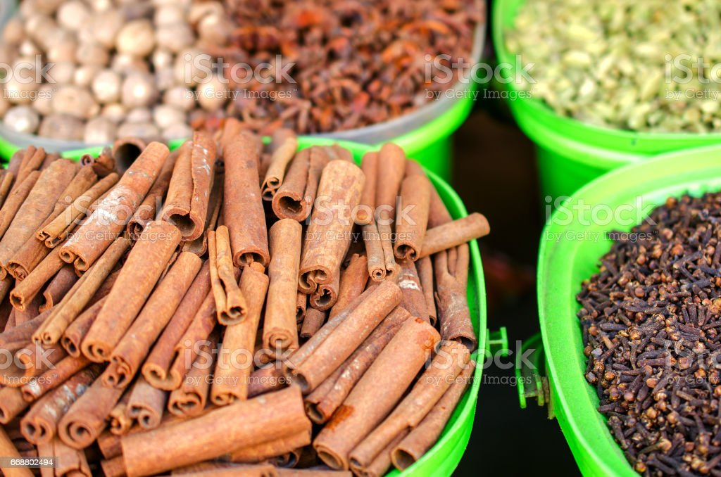 Cinnamon and other spices on the market in colorful containers. stock photo