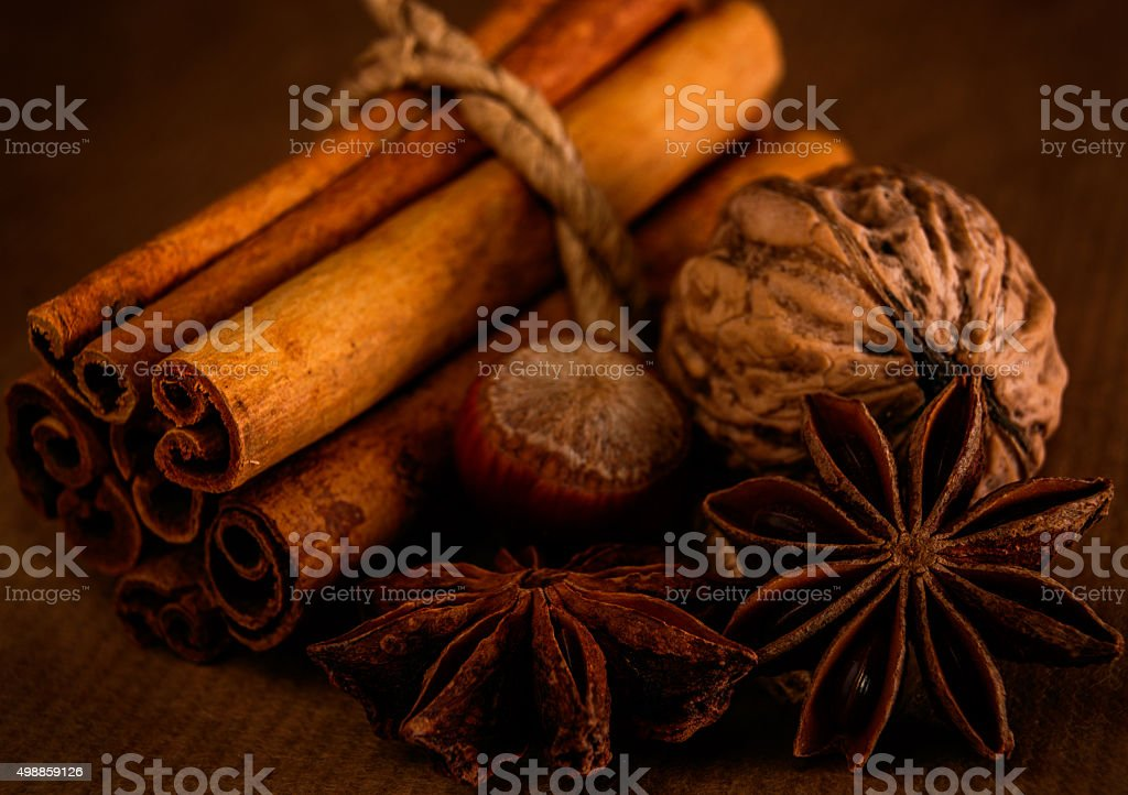 Cinnamon, anise and nuts on a brown background. stock photo