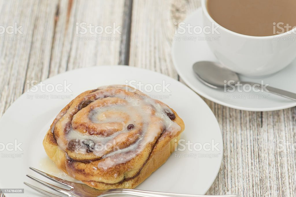 Cinnamon bun on a white plate with coffee royalty-free stock photo