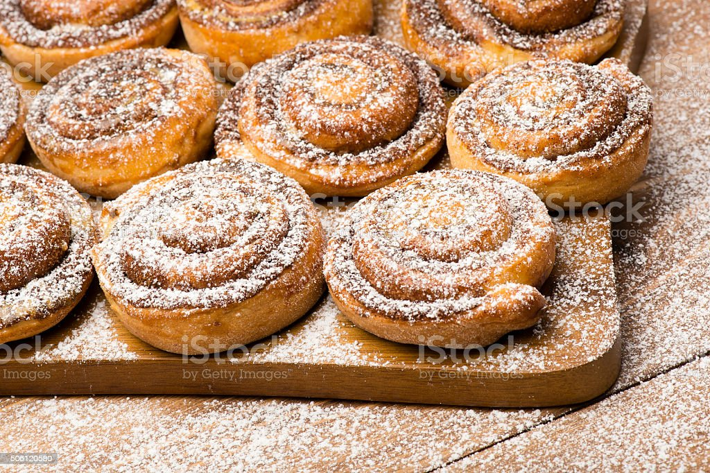 Cinnamon buns on the wooden board. stock photo