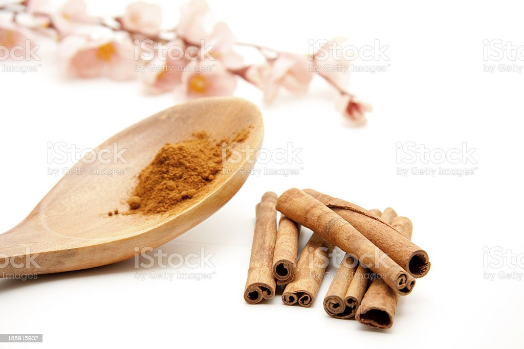Cinnamon ground on wooden spoon and sticks royalty-free stock photo