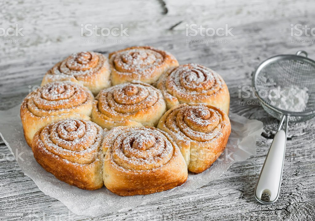 cinnamon rolls on bright wooden surface stock photo