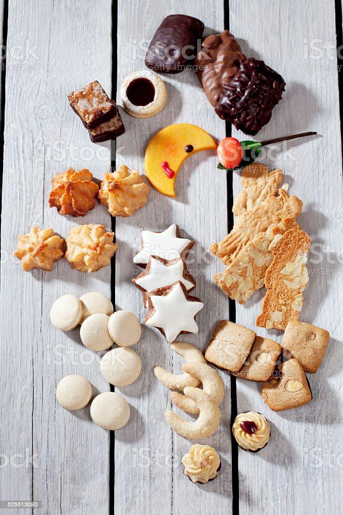 Cinnamon stars, macaroon, spritz cookie, gingerbread on wooden background stock photo