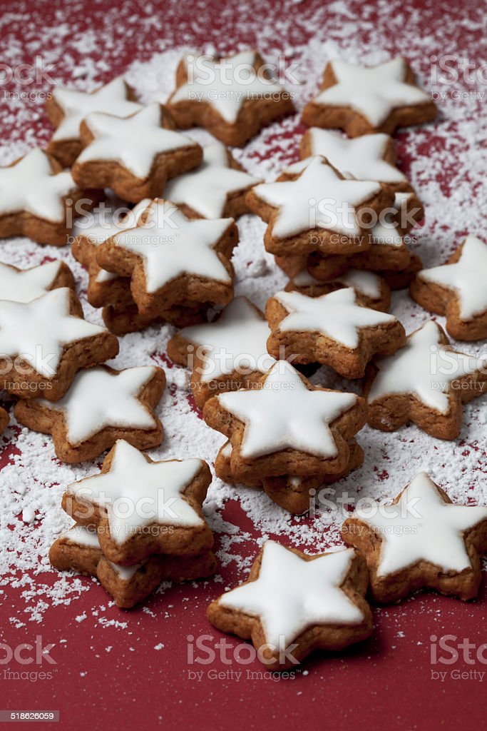 Cinnamon stars sprinkled with powder sugar on red background stock photo