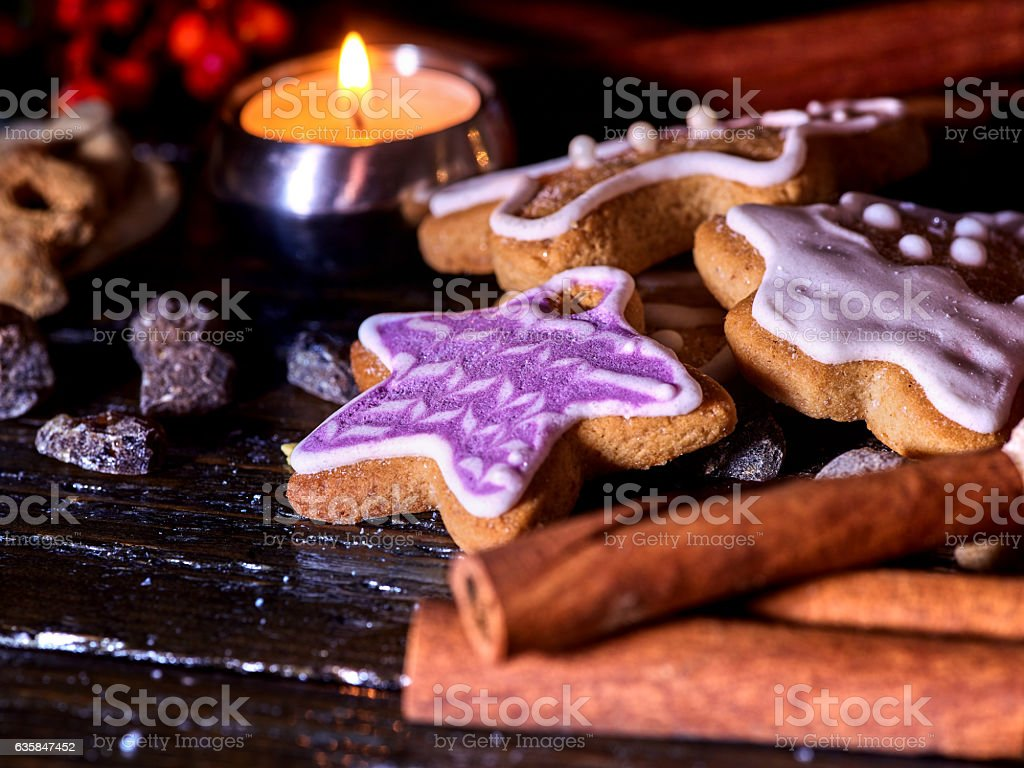 Cinnamon stick background with Christmas gingerbread man on wooden table stock photo
