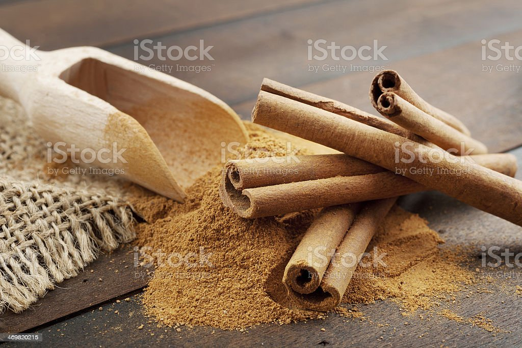 Cinnamon sticks and powder in wooden scoop stock photo