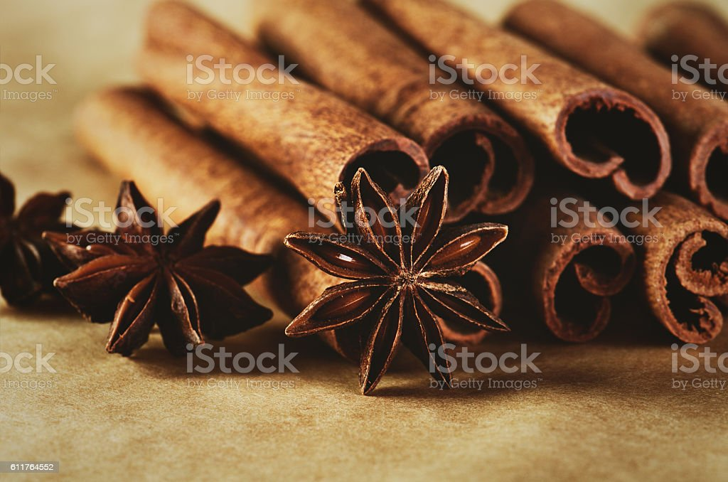 cinnamon sticks and three stars anise on brown paper background stock photo
