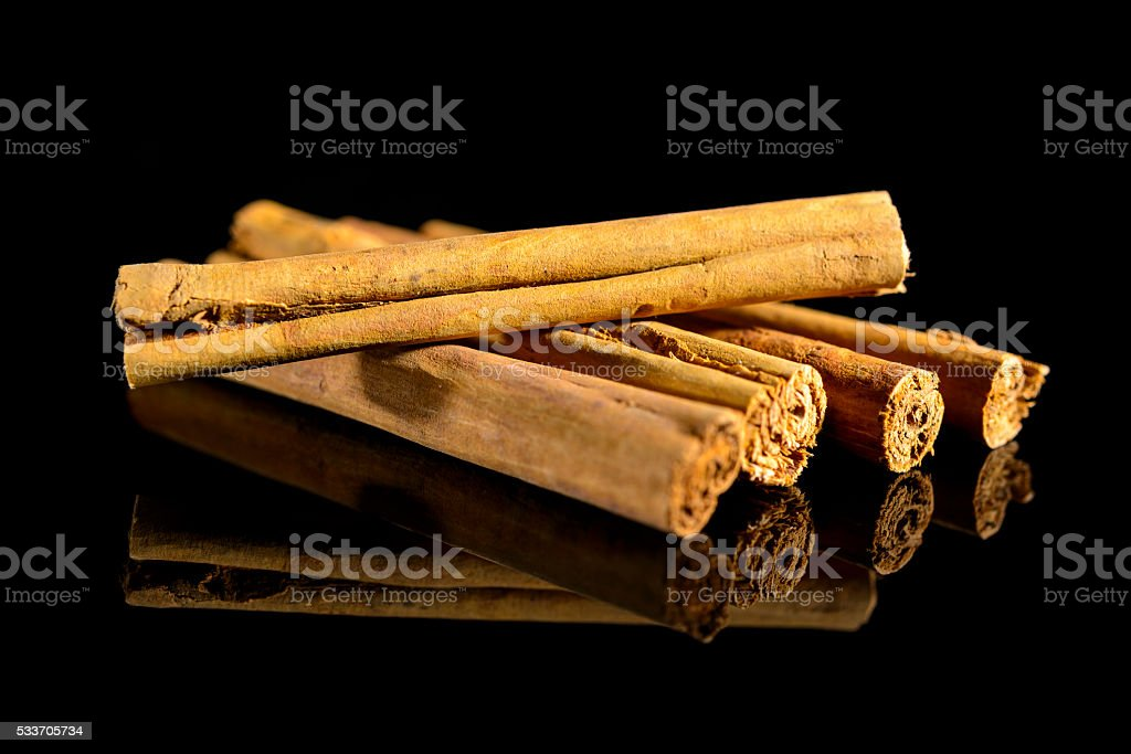 Cinnamon sticks isolated on a black background with reflection stock photo