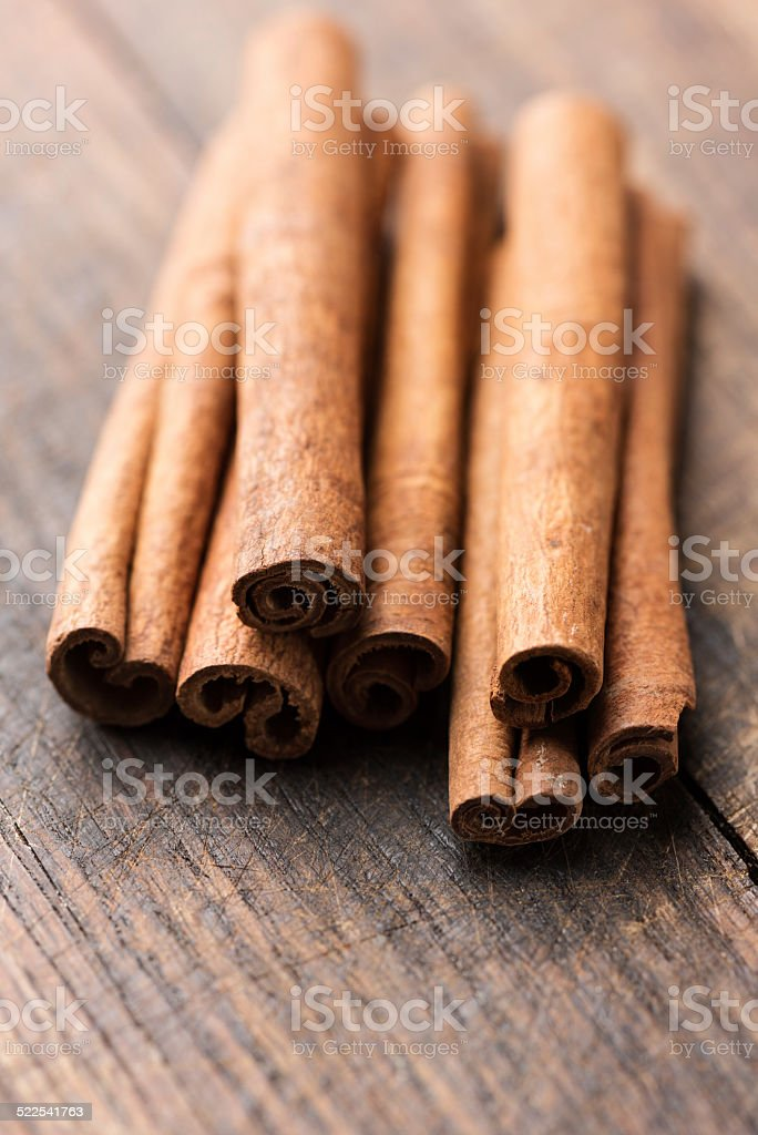 Cinnamon sticks on rustic wooden background stock photo