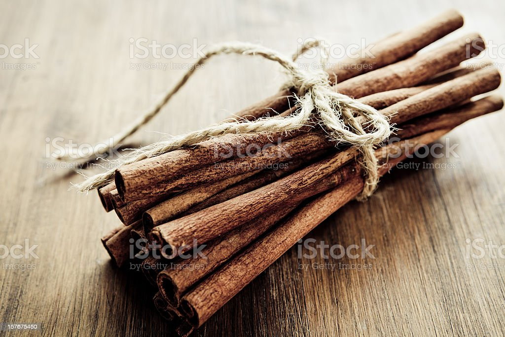 Cinnamon sticks tied together on wood surface royalty-free stock photo