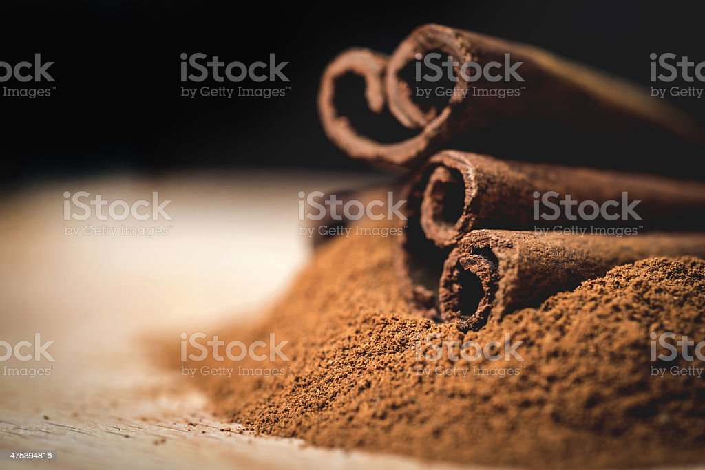 Cinnamon sticks with cinnamon powder on wooden background, Selective focus stock photo