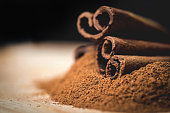 Cinnamon sticks with cinnamon powder on wooden background, Selective focus