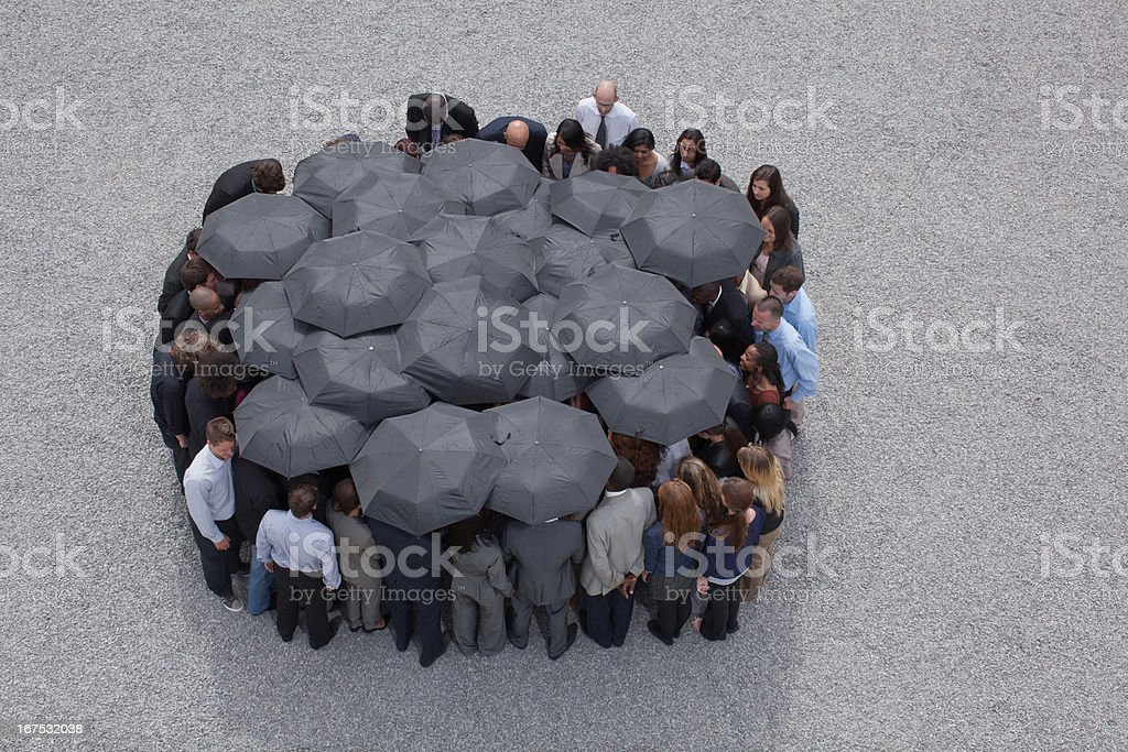 Circle formed by business people with umbrellas stock photo