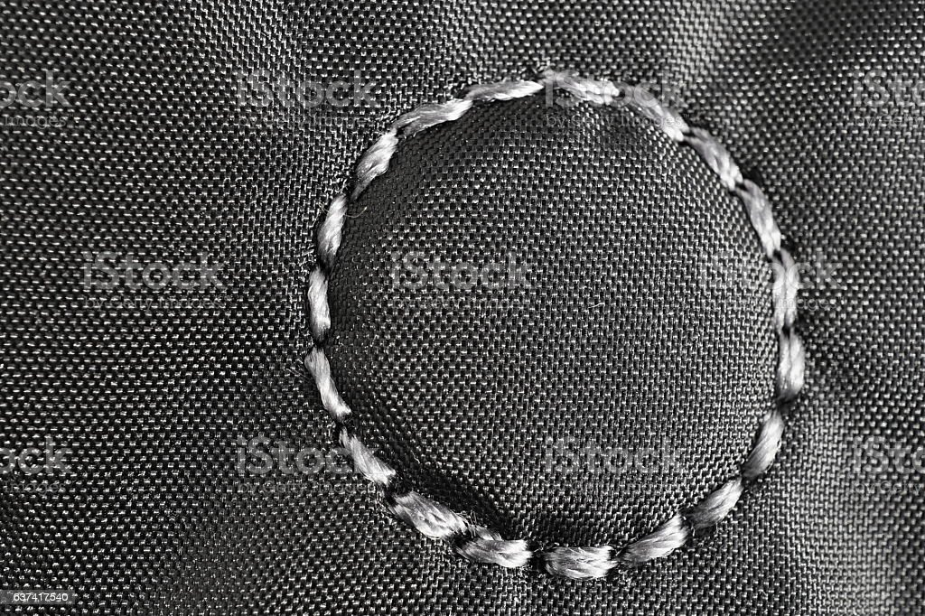 Circle made of stitched thread on the glossy fabric stock photo