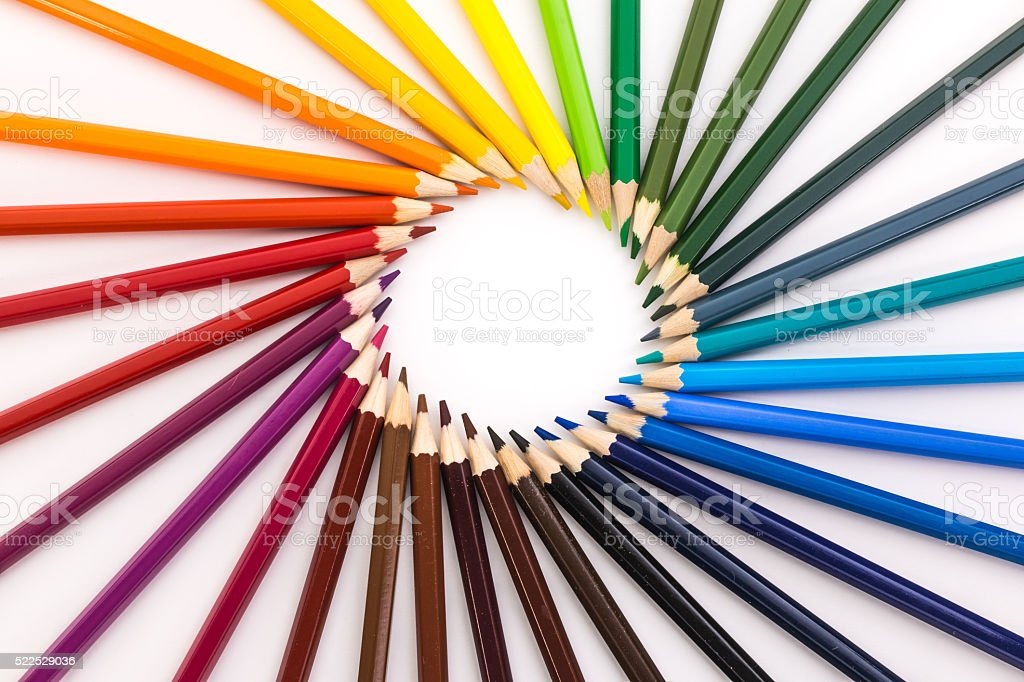circle of colored pencils on white background stock photo