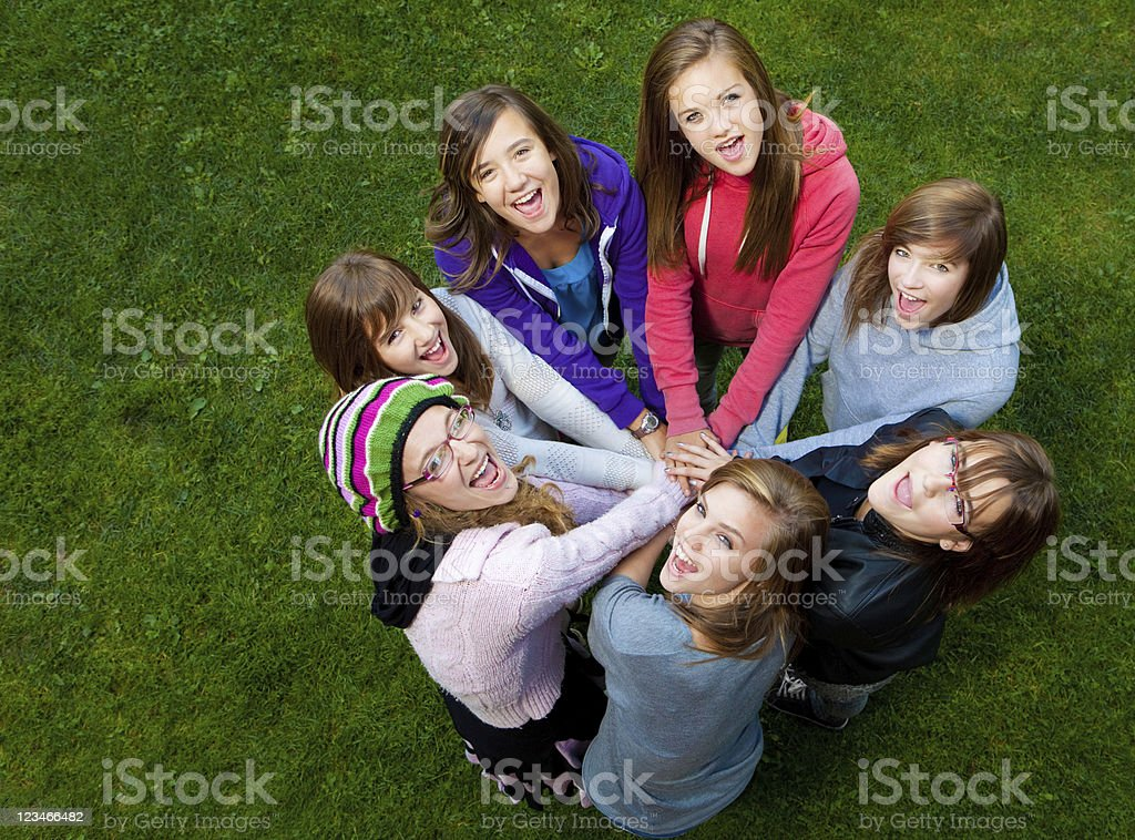 Circle of girls smiling with their hands in center royalty-free stock photo