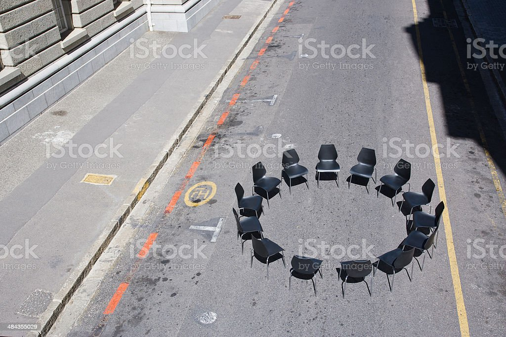 Circle of office chairs in roadway stock photo