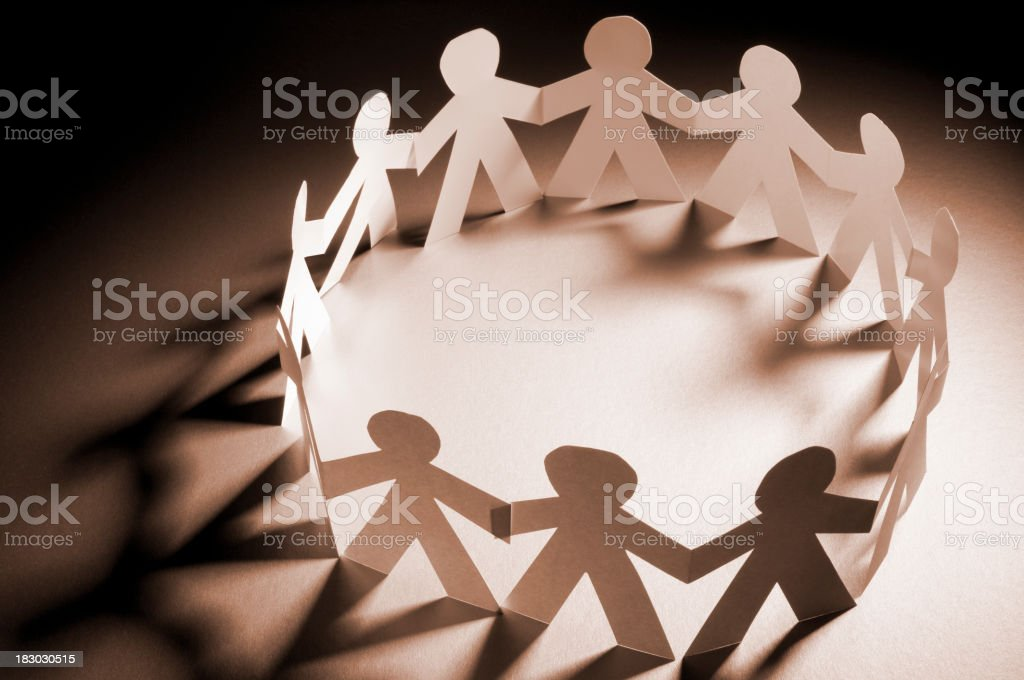 Circle of paper chain people holding hands in spotlight royalty-free stock photo