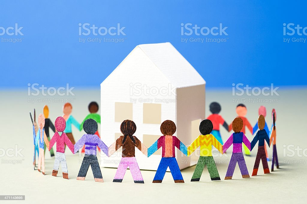 Circle of people around a white house stock photo