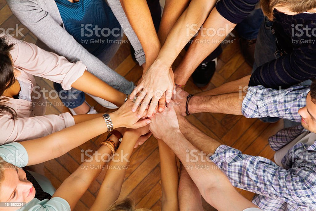 Circle of people with their hands in the center stock photo