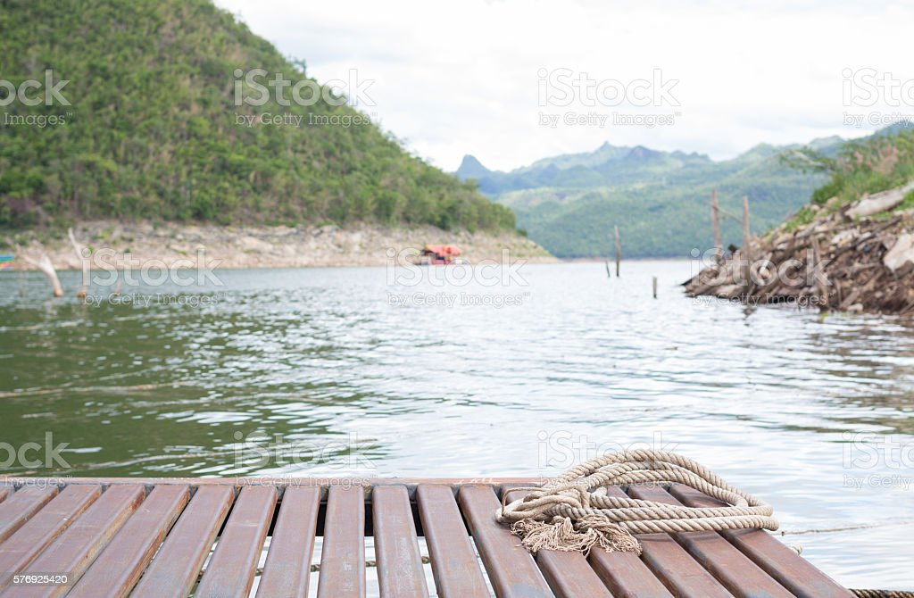 circle of ship rope on old wooden rafting in river Стоковые фото Стоковая фотография