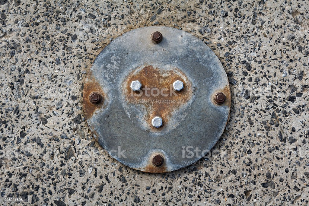 Circle Rusty Metal Piece Bolted Into Gravel Rock Detail stock photo