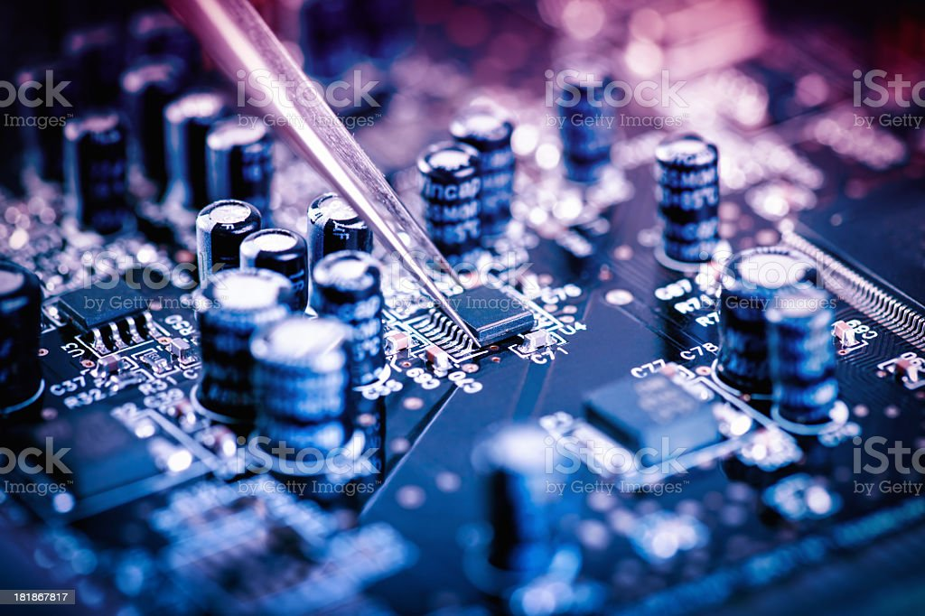 Circuit board being carefully assembled with tweezers stock photo