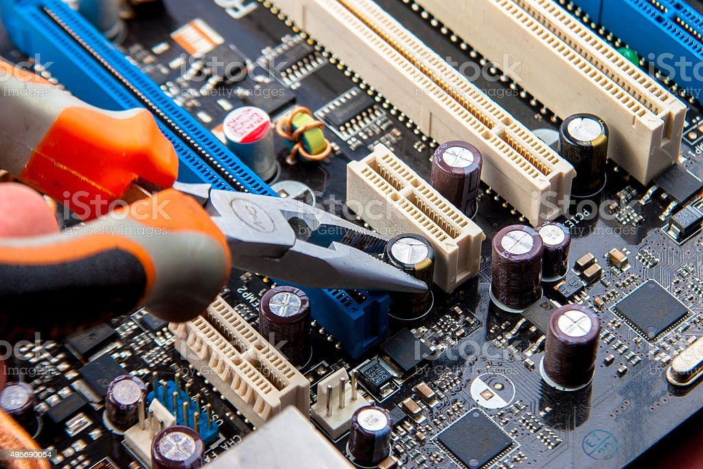 Circuit board with copper radiators and pliers stock photo