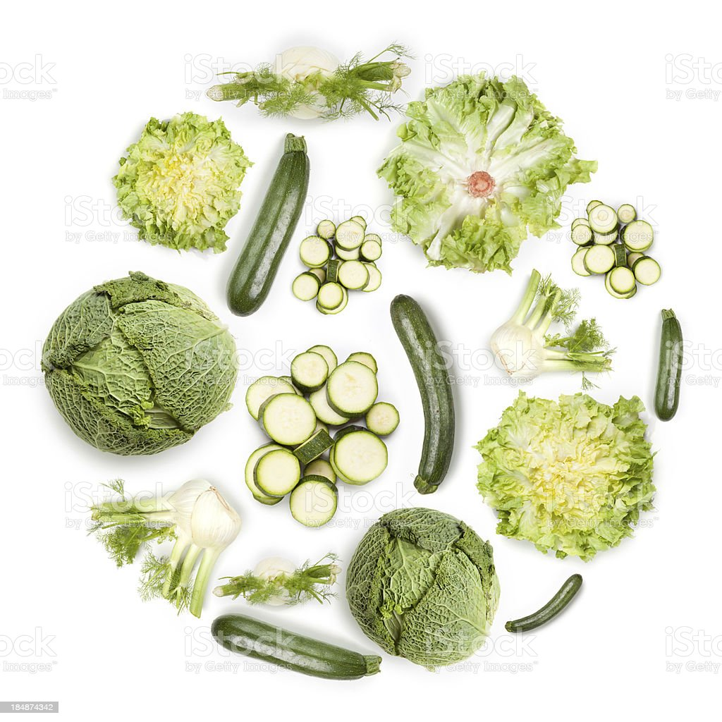Circular arrangement of greens and vegetables on white background royalty-free stock photo