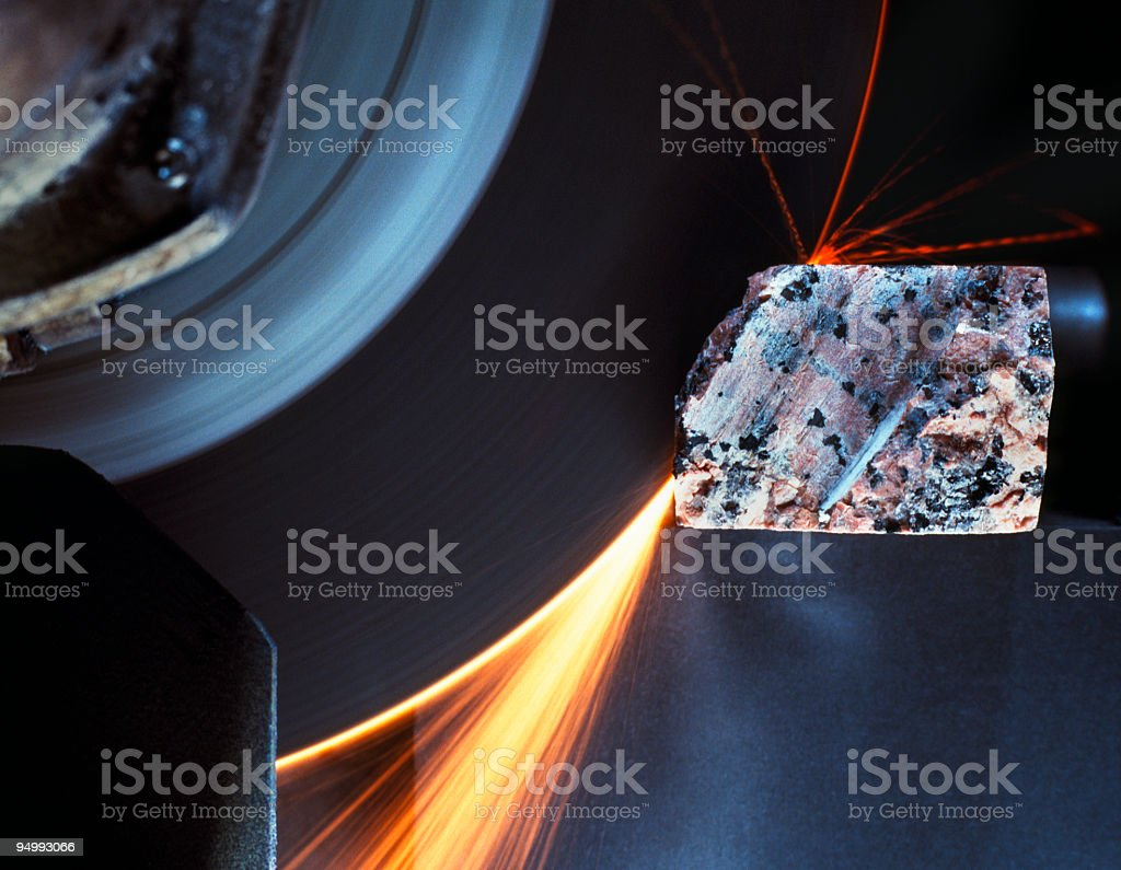 Circular saw cutting the stone, giving off sparks, close-up royalty-free stock photo