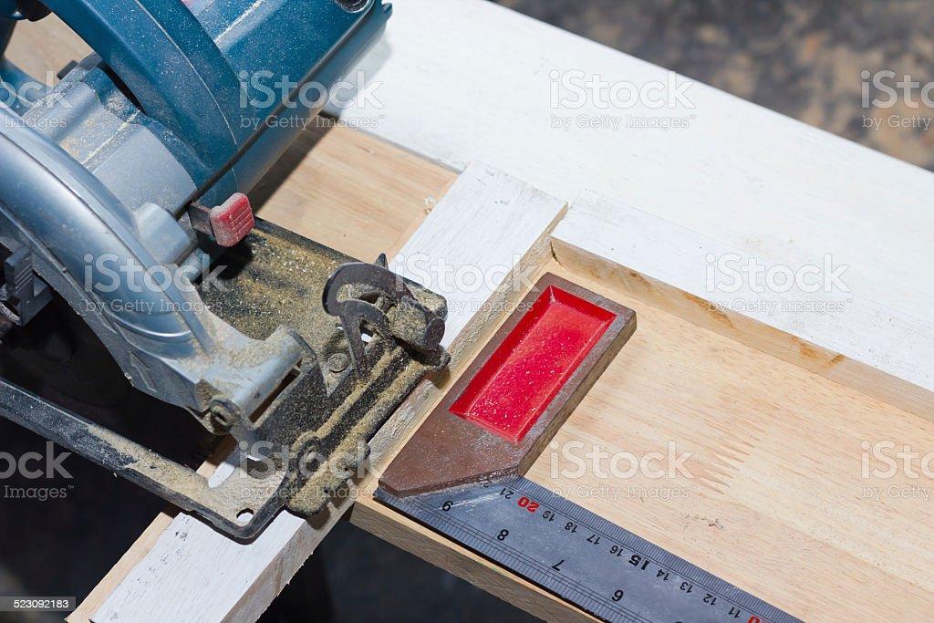 circular saw cutting wood and iron ruler stock photo