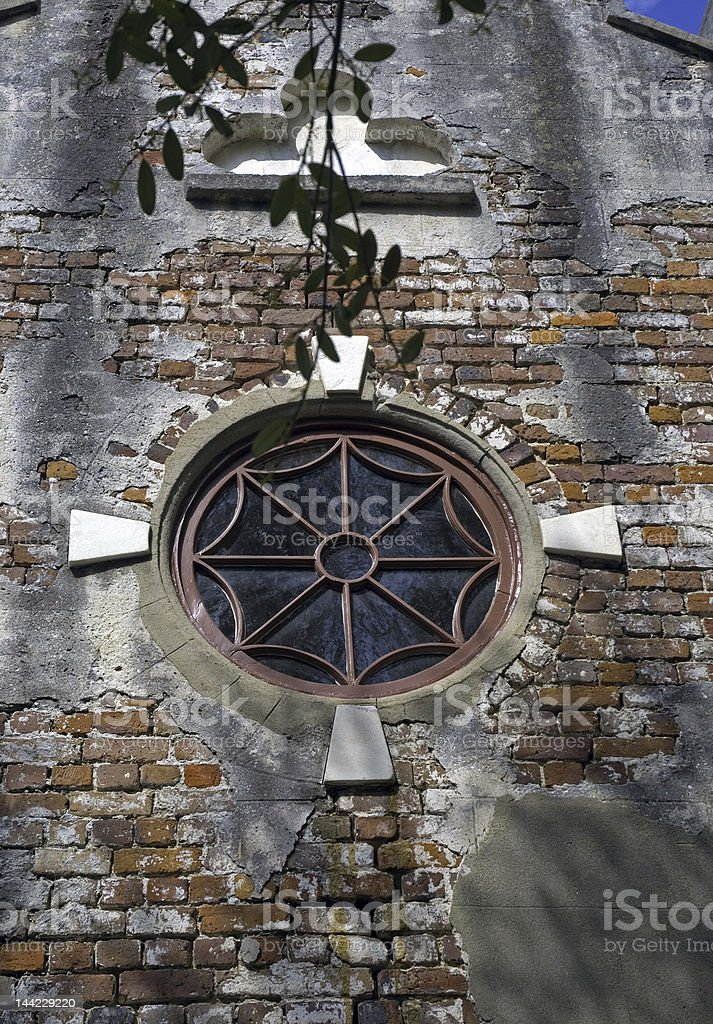Circular Window in a Battered Brick Wall royalty-free stock photo
