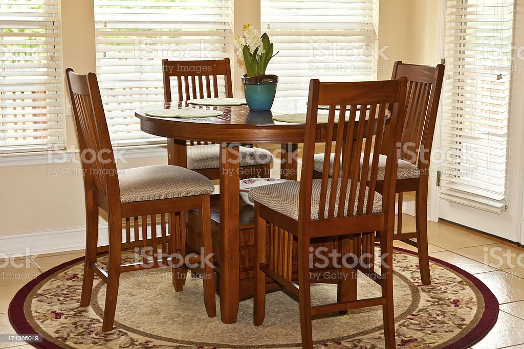 Circular, wooden table that seats four stock photo