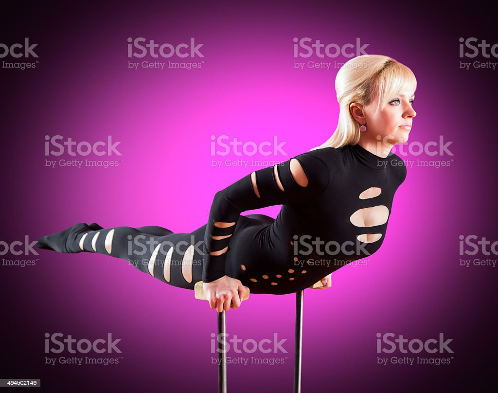 circus actor standing on the hand on a purple background stock photo