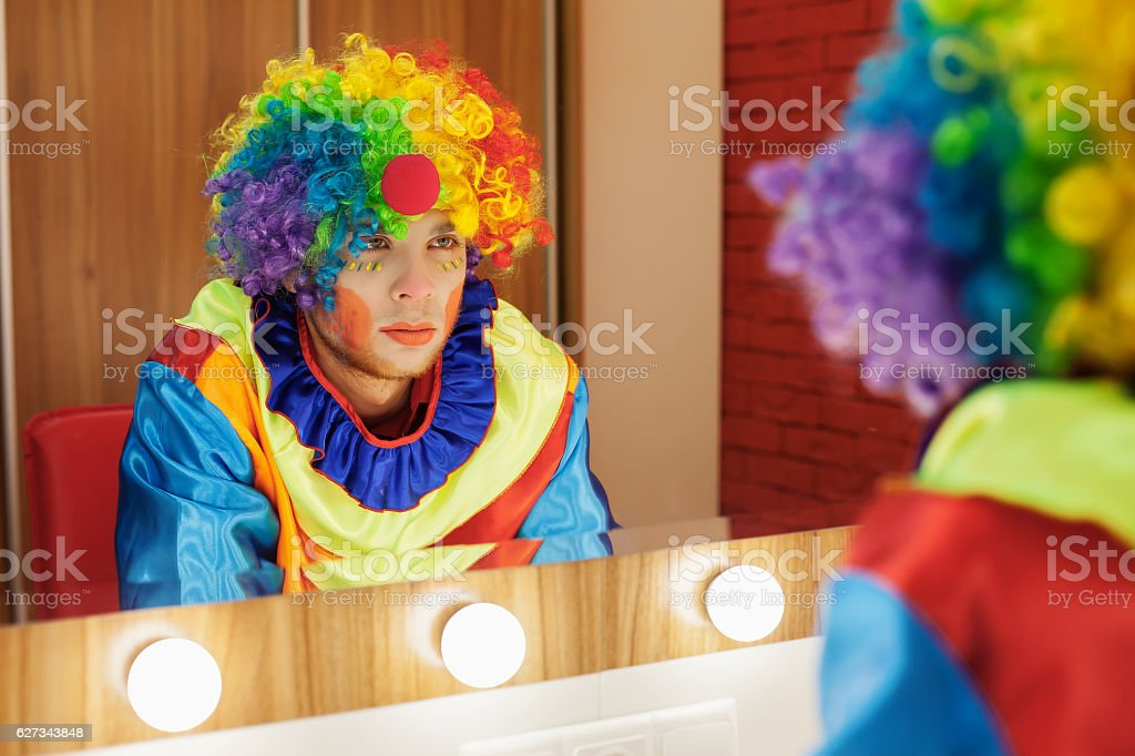 Circus clown looks in a mirror in makeup room. stock photo