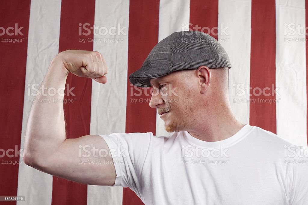 Circus or Carnival Strong Man Flexing His Arm Muscle stock photo