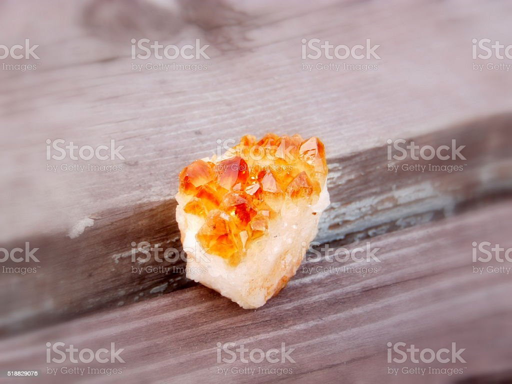 Citrine mineral druze on wooden background stock photo